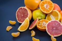 Kulöra citrusfrukter på ett mörker - blå bakgrund Skivor av citruns och peelen Citrus reticulata Citrust paradisi Citrus Limon Arkivbild