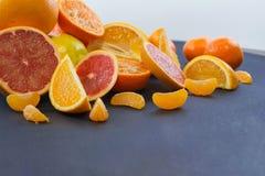 Kulöra citrusfrukter på ett mörker - blå bakgrund Skivor av citruns och peelen Citrus reticulata Citrust paradisi Citrus Limon Royaltyfri Bild