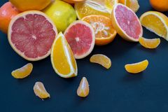 Kulöra citrusfrukter på ett mörker - blå bakgrund Skivor av citruns och peelen Citrus reticulata Citrust paradisi Citrus Limon Fotografering för Bildbyråer