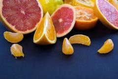 Kulöra citrusfrukter på ett mörker - blå bakgrund Skivor av citruns och peelen Citrus reticulata Citrust paradisi Citrus Limon Arkivfoton
