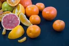 Kulöra citrusfrukter på ett mörker - blå bakgrund Skivor av citruns och peelen Citrus reticulata Citrust paradisi Citrus Limon Arkivfoto