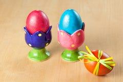 Kulöra easter ägg i äggkoppar Fotografering för Bildbyråer