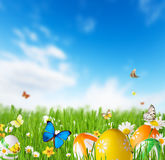 Kulöra easter ägg i gräs med himmelbakgrund fotografering för bildbyråer
