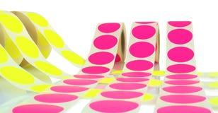 Kulöra etikettrullar som isoleras på vit bakgrund med skuggareflexion Färgrullar av etiketter för skrivare Arkivbild