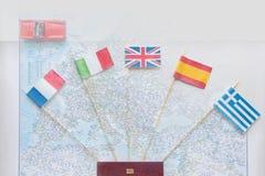 Kulöra flaggor på översikten av Europa: Frankrike Italien, England UK, Spanien, Grekland, loppplan Resa vid bilbegrepp royaltyfria foton