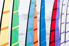 Kulöra flaggor som vinkar i vinden Fotografering för Bildbyråer