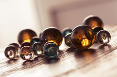 Kulöra glass bollar på en trätabell på en vinkel Glass bollar med reflexion Royaltyfri Bild