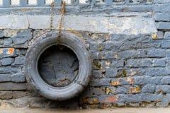 Kulöra gummihjul som hänger på kedjan, har en tegelstenvägg Arkivfoto