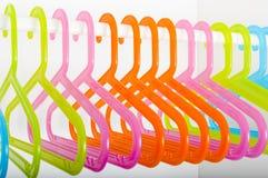 Kulöra hängare på en stång i en garderob Fotografering för Bildbyråer