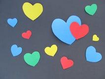 Kulöra hjärtor på en svart bakgrund Arkivbild
