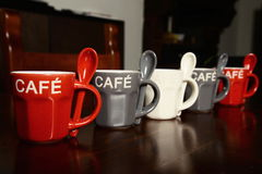 Kulöra kaffekoppar på trätabellen Arkivfoton