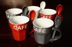 Kulöra kaffekoppar på trätabellen Arkivfoto