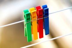 Kulöra klädnypor som hänger på ett rep Arkivfoto