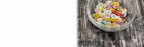 Kulöra knappar i den glass koppen på gammalt träbräde Royaltyfri Foto