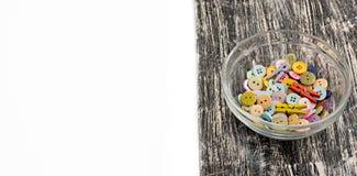 Kulöra knappar i den glass koppen på gammalt träbräde Arkivbilder