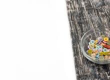Kulöra knappar i den glass koppen på gammalt träbräde Royaltyfria Foton