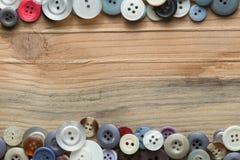 Kulöra knappar på träbräde, färgrika knappar Arkivbilder
