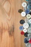 Kulöra knappar på träbräde, färgrika knappar Arkivfoto