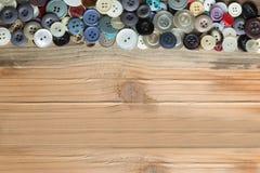 Kulöra knappar på träbräde, färgrika knappar Fotografering för Bildbyråer