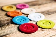 Kulöra knappar på träbräde, färgrika knappar, på gammalt trä Arkivbild