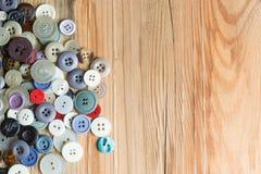 Kulöra knappar på träbräde, färgrika knappar, på gammalt trä Royaltyfria Foton