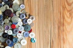 Kulöra knappar på träbräde, färgrika knappar, på gammalt trä Royaltyfri Bild