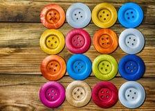 Kulöra knappar på träbräde, färgrika knappar, på gammalt trä Royaltyfri Foto