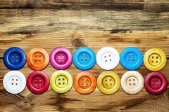 Kulöra knappar på träbräde, färgrika knappar, på gammalt trä Arkivfoto