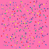 Kulöra konfettier på ljus - rosa bakgrund Royaltyfri Bild