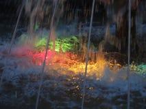 Kulöra ljus i springbrunnen vid natt Arkivbild