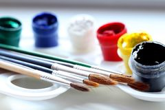 Kulöra målarfärger med borstar på en vit palett royaltyfri fotografi