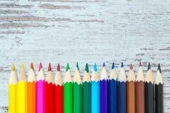 Kulöra mångfärgade blyertspennor stänger sig upp makro ner på tappningen träbakgrund, träslitna bräden med sprickor arkivfoto