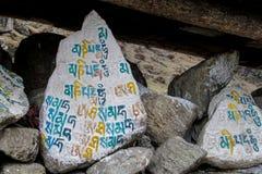 Kulöra Mani Stones med buddistisk mantra i Himalaya, Nepal royaltyfria bilder