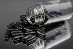 Kulöra medicinska preventivpillerar för svart royaltyfri bild