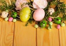 Kulöra påskägg, blommor, godisband, mot bakgrundvän royaltyfria foton