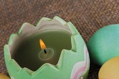 Kulöra påskägg, stearinljus, flamma Arkivfoto