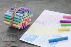 Kulöra pastellfärgade färgpennor på svart backround med målat papper arkivfoto