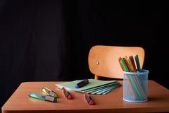 Kulöra pennor i en blå metallkorg på skrivbordet i skola Fotografering för Bildbyråer