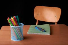 Kulöra pennor i en blå metallkorg på skrivbordet i skola Royaltyfri Bild