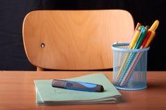 Kulöra pennor i en blå metallkorg på skrivbordet i skola Royaltyfri Foto