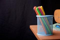 Kulöra pennor i en blå metallkorg på skrivbordet i skola Arkivfoton