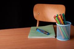 Kulöra pennor i en blå metallkorg på skrivbordet i skola Arkivfoto