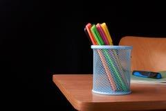 Kulöra pennor i en blå metallkorg på skrivbordet i skola Arkivbilder