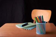 Kulöra pennor i en blå metallkorg på skrivbordet i skola Royaltyfria Bilder