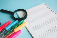 Kulöra pennor och förstoringsapparat på ett vitt ark av notepaden för text Utbildning eller affärsidé arkivfoto