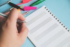Kulöra pennor och förstoringsapparat på ett vitt ark av notepaden för text Utbildning eller affärsidé arkivbilder