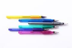 Kulöra pennor på vit bakgrund Arkivbilder