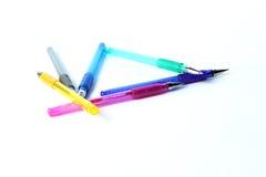Kulöra pennor på vit bakgrund Fotografering för Bildbyråer