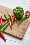 Kulöra peppar för varm chili på ett träbräde royaltyfria bilder