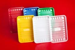 Kulöra plast-plattor på röd bakgrund Royaltyfria Bilder
